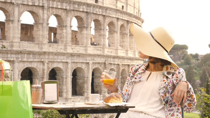 Happy young woman tourist drinking coffee and juice with cornetto at the table outside a bar restaurant in front of the Colosseum in Rome. Elegant beautiful dress with large hat and colorful shopping