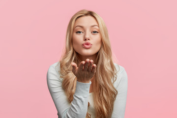 Beautiful woman with makeup and long blonde hair blows kiss, demonstrates her good feelings, says goodbye on distance, isolated over pink background. Young pretty female model makes air kiss.