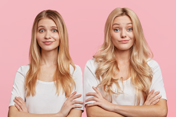 Beautiful female and her younger sister keep arms folded, watch attentively film online, express different emotions and facial expressions, stand next to each other against pink studio background