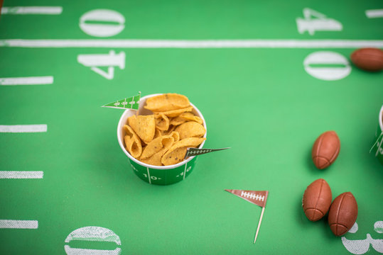 closeup of paper bowl of corn chips on green field with yard lines for big game