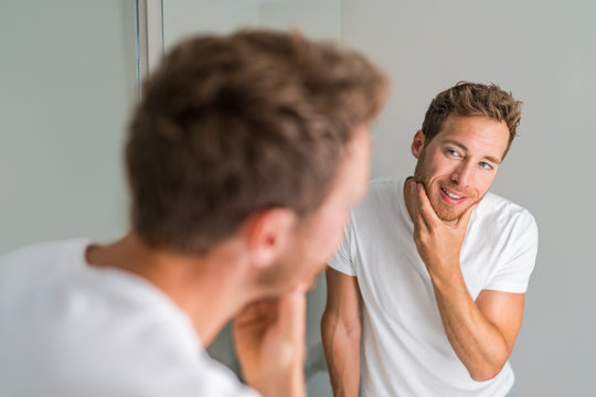 Male beauty young man touching beard and face looking in mirror - healthy skin. Skincare in home bathroom. After shave men lifestyle shaving concept.
