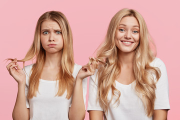 Isolated shot of cheerful blonde female and her companion blows cheeks as touches hair, being dissatisfied with her new shampoo, isolated over pink background. Two friends meet together, gossip