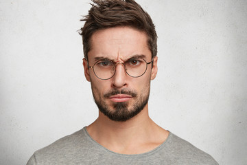 Close up portrait of irritated grumpy male with trendy hairstyle looks angrily through spectacles, expresses negative emotions, being annoyed with someone, poses against white concrete wall.