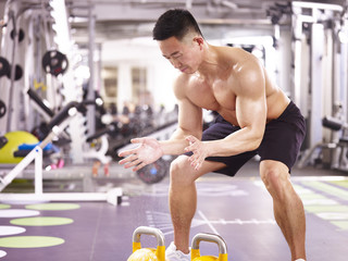 asian bodybuilder exercising in gym