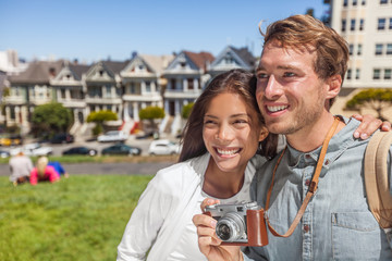 San Francisco Painted Ladies houses people tourists on America summer trip holidays taking photos, Young multiethnic couple asian woman, caucasian man.