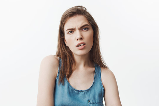 What did you say? Young beautiful dark-haired student girl in blue shirt looking in camera with mean and aggressive expression after hearing offencive words from popular girl in university.