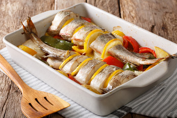 cod baked with pepper, tomatoes, onions and lemon in a baking dish close-up. horizontal