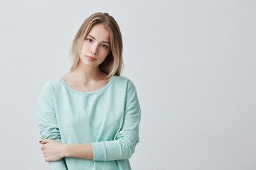 Portrait of young tender blonde european woman with healthy skin wearing light blue long-sleeved looking at camera with calm or pleasant expression. Caucasian female model posing indoors