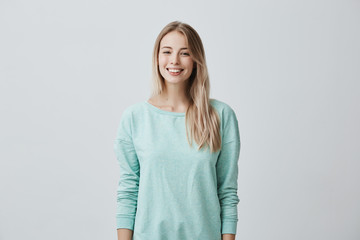 European female model with long blonde hair, wears light blue sweater, looks at camera with dreamful and positive expression imagines or remembers pleasant moments spent with boyfriend.