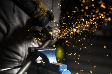 Close up of welder welding motorbike pipe in workshop