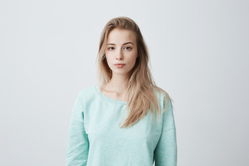 People and lifestyle. Studio shot of attractive young Caucasian dark-eyed female with long dyed blonde hair posing against gray blank wall dressed in casual blue sweater with calm face expression.