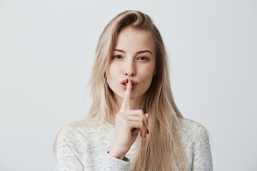 Shot of beautiful female with long blonde dyed hair wears casual long-sleeved t-shirt, shows hush sign, has serious expression, asks not to tell her secret anybody, hopes for loyality and silence.
