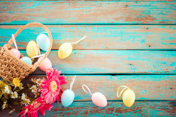 Wall Mural - Colorful Easter eggs with flower on rustic wooden planks background in blue paint. Holiday in spring season. vintage color tone style. top view composition.