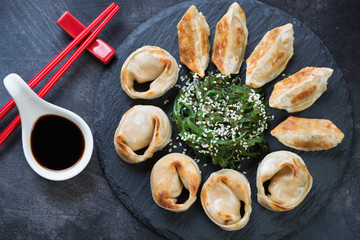 Above view of a stone slate with fried asian dumplings, chuka salad and dipping sauce, close-up