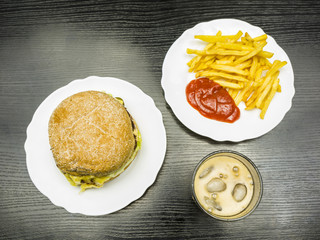 Fast food set - beef burger, french fries with ketchup and cola with ice. View from above.