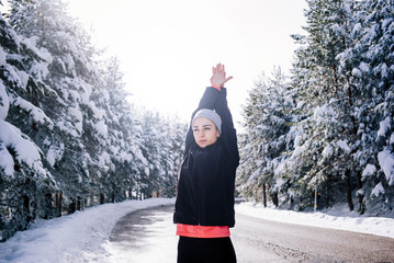 Young woman does exercise in snowy area.