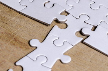 the unexpected solution, white jigsaw/puzzle with a row in wrong position, over  wooden table background, symbol of problem solving and new vision