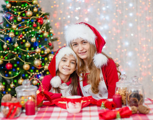Mom and daughter in Christmas hats sitting at a festive table