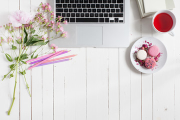 Feminine flat lay workspace with laptop, cup of tea, macarons and flowers on white wooden table. Top view mock up.