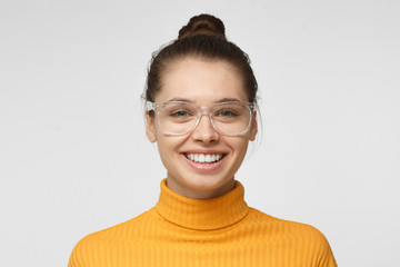 Close up shot of smiling and laughing attractive young woman in yellow polo neck sweater and transparent eyeglasses isolated on gray background