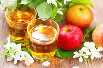 Sweet apple juice, apples and flowers on the table