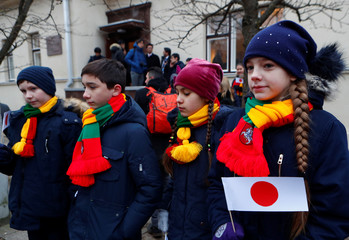 Children hold Japanese flags as they wait for Japan's Prime Minister Shinzo Abe, in Kaunas