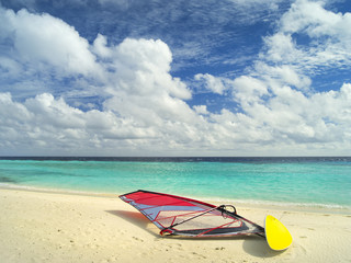 wind surfing board on the sand beach in front of emerald sea on Maldives island in sun shining day