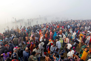"""Hindu devotees gather to take a holy dip at Sangam, the confluence of the Ganges, Yamuna and Saraswati rivers, on a foggy winter morning on the occasion of """"Makar Sankranti"""" festival in Allahabad"""