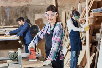 Frau als Lehrling schleift Holz