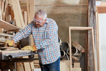 Senior als Schreiner schleift Holz