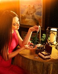 Woman over jewelry box puts necklace on her neck . Romantic evening on luxary interior background. Symbols of past life. Woman says goodbye to gone love. Nostalgia.