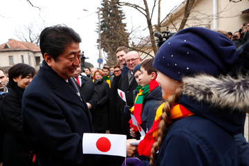 Japan's Prime Minister Shinzo Abe greets children holding Japanese flags, as he arrives to visit a former home of Chiune Sugihara, a Jew-saving Japanese diplomat in Kaunas