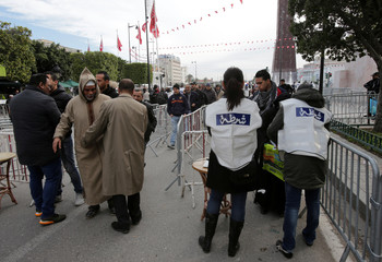 Police check demonstrators as they arrive during demonstrations on the seventh anniversary of the toppling of president Zine El-Abidine Ben Ali, in Tunis