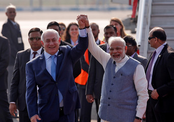 Israeli Prime Minister Benjamin Netanyahu and his Indian counterpart Narendra Modi raise their arms upon Netanyahu's arrival at Air Force Station Palam in New Delhi