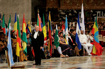 A Vatican gentleman stands in front of migrants holding their countries' flags as they wait for the arrival of Pope Francis to lead a special mass to mark International Migrants Day in Saint Peter's Basilica at the Vatican