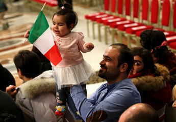 A migrant holds his child waving an Italian flag as they wait for Pope Francis to lead a special mass to mark International Migrants Day in Saint Peter's Basilica at the Vatican