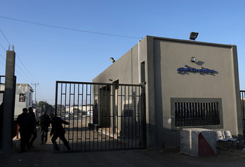 Palestinian security man closes the gate outside Kerem Shalom, the main passage point for goods entering Gaza, after it was shut down by Israel, in the southern Gaza Strip