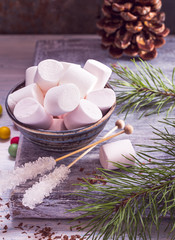 Bowl of marshmallow and sugar sticks on table