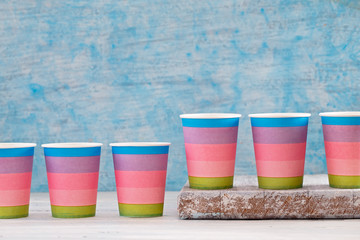 Multicolored disposable paper cups in row on blue background, abstract concept