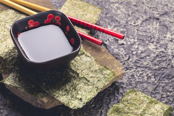 Japanese style soy sauce bowl and chopsticks on dark stone background with copy space