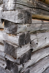 Angle of old wooden house of grey logs stacked on top of each other.