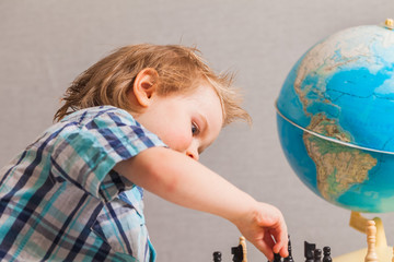 boy in blue shirt playing chess on the table is a globe