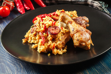 Traditional paella with chicken legs, sausage chorizo and vegetables served on black plate