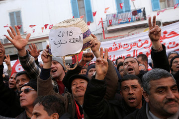 People shout slogans during demonstrations on the seventh anniversary of the toppling of president Zine El-Abidine Ben Ali, in Tunis