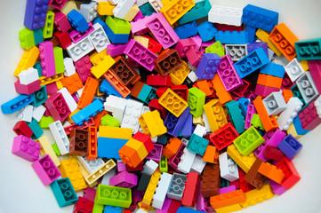 Childrens Designer Background. Multicolored plastic building blocks of the designer.