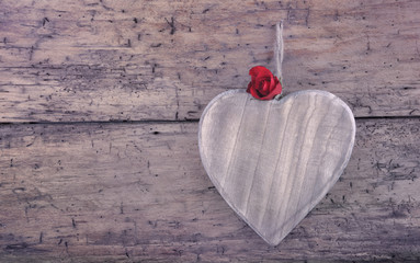 little rose on a  wooden heart hanging on a rustic plank with vintage effect