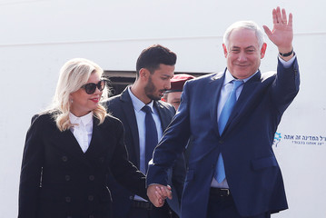 Israeli Prime Minister Benjamin Netanyahu waves as his wife Sara watches upon their arrival at Air Force Station Palam in New Delhi