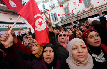 Women shout slogans during demonstrations on the seventh anniversary of the toppling of president Zine El-Abidine Ben Ali, in Tunis