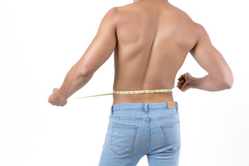 Close up upper part of sexy young Asian muscular man in blue jean trousers holding plastic tape measure around his waist isolated on white background