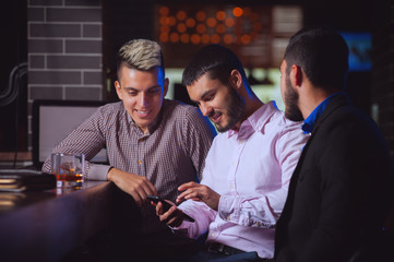 Young positive man shows photos of his family to two of his old friends sitting in bar